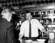 A rather stern-looking publican, behind the bar of the 'Jolly Fenman' pub, Sidcup, Kent, England. Date: 1965